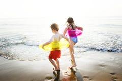与赛跑者的孩子敲响使用在海滩 库存图片