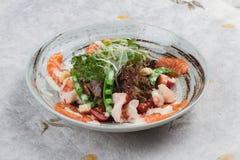 与赤栎,豌豆,与蛋黄酱顶部的油煎方型小面包片的三文鱼和虾沙拉与在墨水的狂放的火箭绘了在washi的陶瓷碗 免版税库存图片