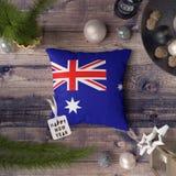 与赫德岛和麦克唐纳群岛旗子的新年快乐标记在枕头 在木桌上的圣诞装饰概念与可爱 库存图片