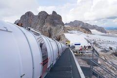 与走到Dachstein冰川的人的滑雪电缆车 免版税库存图片
