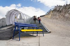 与走到Dachstein冰川的人的滑雪电缆车 免版税库存照片
