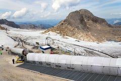 与走到Dachstein冰川的人的滑雪电缆车 库存图片