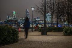 与走在晚上的一名无法认出的妇女的伦敦地平线 库存照片