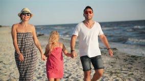 与走在海滩的小女儿的愉快的家庭握手在海边的暑假时 股票录像