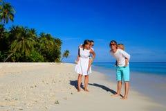 与走在海滩的两个孩子的年轻家庭 免版税库存照片