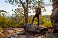 与走在澳大利亚bushland的背包的女性bushwalker 免版税图库摄影