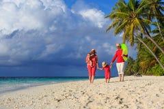 与走在热带海滩的孩子的家庭 库存照片