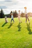 与走在绿色草甸的金毛猎犬狗的愉快的年轻家庭 图库摄影