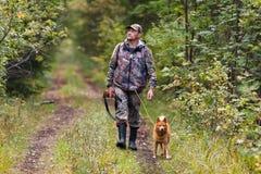 与走在路的狗的猎人 免版税库存照片