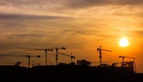 与起重机剪影的工业风景在日落的 免版税库存照片