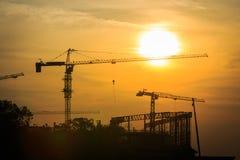 与起重机剪影的工业风景在日落的 免版税库存图片
