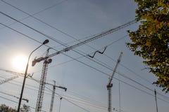 与起重机和输电线,城市建筑概念剪影的工业风景  库存照片
