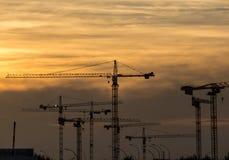 与起重机的工业日落在建造场所 免版税库存照片