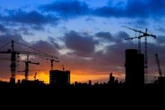 与起重机的建筑工地剪影在日落 免版税库存照片