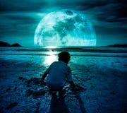 与超级月亮的夜空 开掘在沙子的女孩 conn的概念 库存照片