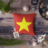 与越南旗子的新年快乐标记在枕头 在木桌上的圣诞装饰概念与可爱的对象 免版税库存照片