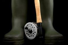 与趟过起动的用假蝇钓鱼标尺和卷轴在黑背景 图库摄影