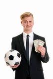与足球和金钱的年轻商人 免版税图库摄影
