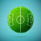 与足球场的绿草球形在蓝色清楚的背景 库存照片