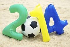 与足球橄榄球的五颜六色的2014年消息在海滩 库存图片