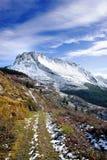 与足迹的冬天风景往多雪的山 免版税库存照片