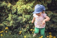 与跑在树和花中的草甸的嬉戏的快乐的儿童女孩的无忧无虑的童年在暑假期间 免版税库存图片