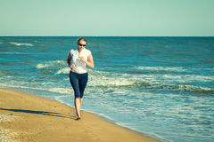 与跑步在海滩的赤脚的妇女佩带的玻璃 免版税库存图片