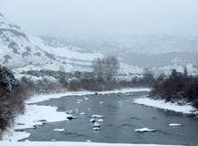 与跑通过多雪的风景的科罗拉多河的冷漠的场面 免版税库存图片