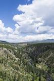 与跑通过它的河的谷和蓝天和云彩 免版税库存照片