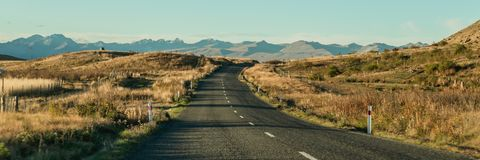 与路和蓝天, Otago,新西兰的山风景 免版税图库摄影
