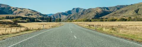 与路和蓝天, Otago,新西兰的山风景 免版税库存照片