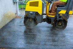 与路辗压紧机机器和沥青修整机的道路施工工作涂柏油汽车的停车处 库存图片