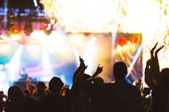 与跳舞青年人的剪影的明亮的五颜六色的背景在表现喜爱音乐家期间 库存照片