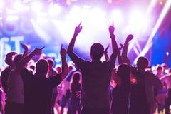 与跳舞青年人的剪影的明亮的五颜六色的背景在表现喜爱音乐家期间 图库摄影