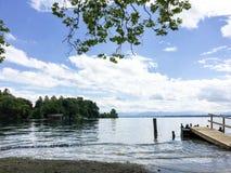 与跳船和树木丛生的岸的平静的海岸场面 库存图片