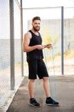 与跳绳的愉快的有胡子的健身人锻炼 库存图片