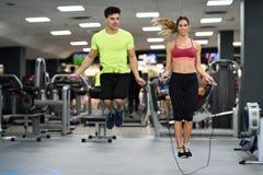 与跳绳的男人和妇女锻炼在crossfit健身房 库存图片