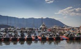 与身分游艇和喷气机的停泊处在山背景滑雪  免版税库存照片