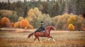 与车手的马狩猎在女骑装 免版税库存照片