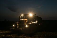 与车灯的拖拉机门在夜间 库存图片