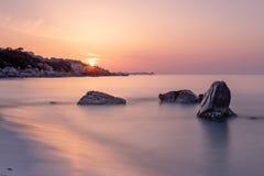 与软性波浪和橙色天空与太阳,撒丁岛意大利的日出风景 图库摄影