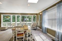 与软的蓝色帷幕和花卉地毯的好的餐厅内部 图库摄影
