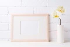 与软的黄色兰花的木风景框架大模型在花瓶 免版税库存照片