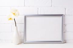 与软的黄色兰花的银色风景框架大模型在花瓶 库存图片