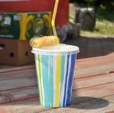 与软饮料的一块五颜六色的塑料玻璃和在一个长木凳的一个小的小圆面包浮出水面 库存图片