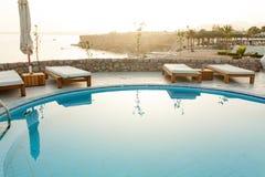与轻便马车休息室的在热带手段的游泳池和遮光罩 库存照片