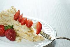 与轻松的事的一把叉子在板材的拿破仑装饰用一个红色成熟草莓 免版税库存照片