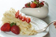 与轻松的事的一把叉子在板材的拿破仑,装饰用一个红色成熟草莓,在一个碗后用莓果 免版税库存照片