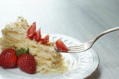 与轻松的事的一把叉子在板材的拿破仑,装饰用在桌上的一个红色成熟草莓 库存照片