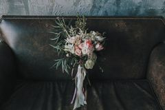 与轻的玫瑰和其他花的土气婚礼花束在豪华棕色沙发 特写镜头 免版税库存图片